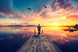 Lonely man on wooden pier contemplating a colorful sunset reflected on the sea with two flamingos flying high.