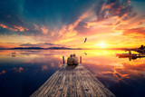 Senior couple seated on a wooden jetty, looking a colorful sunset on the sea with a flying flamingo reflected on the calm water.