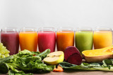 Glasses with different juices and fresh ingredients on light background