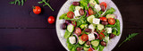 Greek salad with fresh vegetables, feta cheese and kalamata olives. Healthy food. Banner. Top view