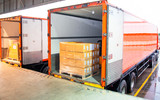 Road freight industry logistics and transportation. Warehouse dock cargo shipment load into truck container shipping, stack package boxes wrapping plastic on pallet load into a truck.