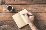 Proste miejsce pracy. Drewniany stół biurkowy z ręcznym zapisem na pustym notatniku i kawą. Poranna koncepcja planowania.
