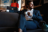 Handsome young man holding coffee cup sitting on the couch in office