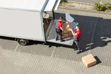 Male Movers Unloading The Cardboard Boxes Form Truck