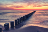 Baltic sea seascape at sunset, Poland, wooden breakwater and waves