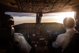 Piloten im Cockpit bei Sonnenaufgang