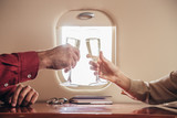 cropped view of boyfriend and girlfriend clinking with champagne glasses in private plane