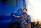 Truck driver occupation. Middle aged bearded trucker standing by his semi truck vehicle ready for work. Transporting and delivering goods. Transportation services.