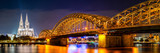 Panorama of the Hohenzollern Bridge over the Rhine River and Cologne Cathedral by night
