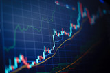 Closeup financial chart with uptrend line candlestick graph in stock market on blue color monitor background