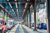 Bottom view of Elevated train track nyc. Traffic waiting in road in a sunny day. Travel and traffic concepts. Bronx, NYC, USA