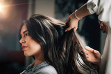 Hairstylist Fixing Woman's Hair