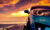 Blue compact SUV car with sport and modern design parked on concrete road by the sea beach at sunset. Front view of luxury car. Closeup SUV fog lamp and headlights with beautiful sunset sky in summer.