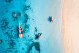 Aerial view of the fishing boats in clear blue water at sunset in summer. Top view from drone of boat, yacht, sandy beach in Zanzibar. Travel. Tropical seascape with sailboats, sea. View from above