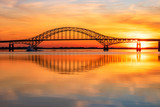 Steel tied arch bridge spanning a bay with crystal clear reflections in the water at sunset. Fire Island Inlet Bridge, part of the Robert Moses Causeway on Long Island New York.