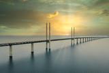 The Oresund bridge between Copenhagen Denmark and Malmo Sweden during sunset over the sea.