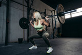 Young blonde woman with barbell flexing muscles and making shoulder press squat.