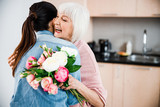 Cheerful old lady holding flowers and hugging granddaughter