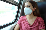 Travel safely on public transport. Young woman with KN95 FFP2 face mask looking through train window. Train passenger with protective mask.