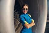 Happy pretty stewardess near large passenger plane