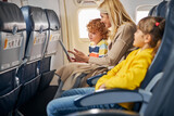 Woman inside a plane showing a tablet to a boy
