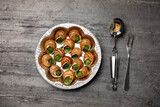 Delicious cooked snails served on grey table, flat lay